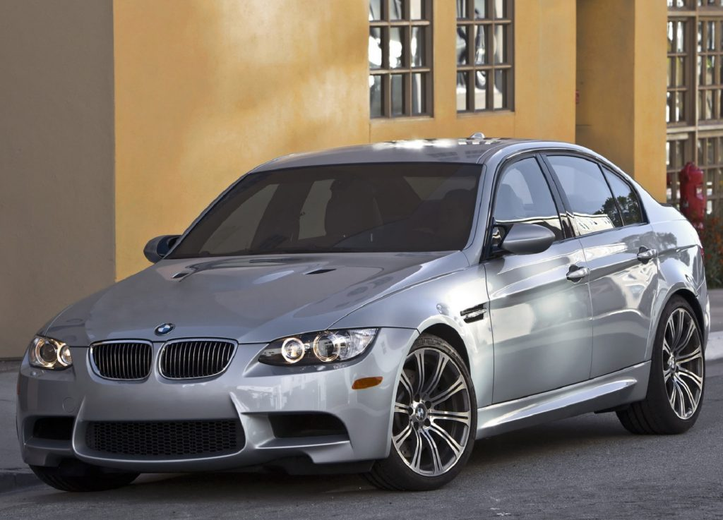 A silver 2008 E90 BMW M3 Sedan by a yellow building