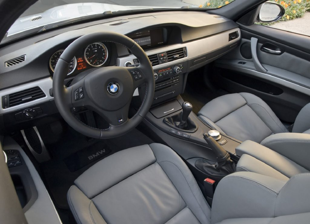 The gray-leather-upholstered front seats and silver dashboard of a 2008 E90 BMW M3 Sedan