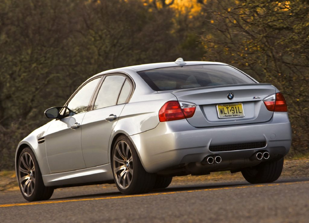 The rear 3/4 view of a silver 2008 E90 BMW M3 Sedan by some trees