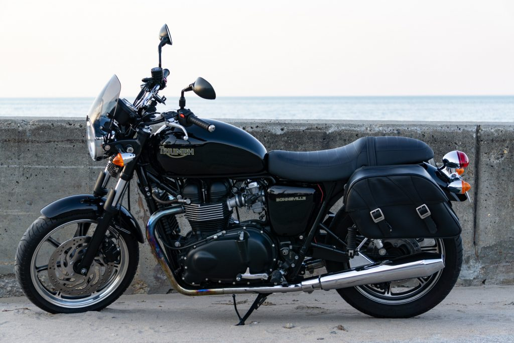The side view of a black 2009 Triumph Bonneville with saddlebags next to a beach-side concrete wall