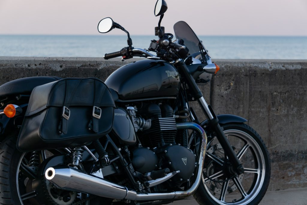 The side 3/4 view of a black 2009 Triumph Bonneville with saddlebags next to a beach-side concrete wall
