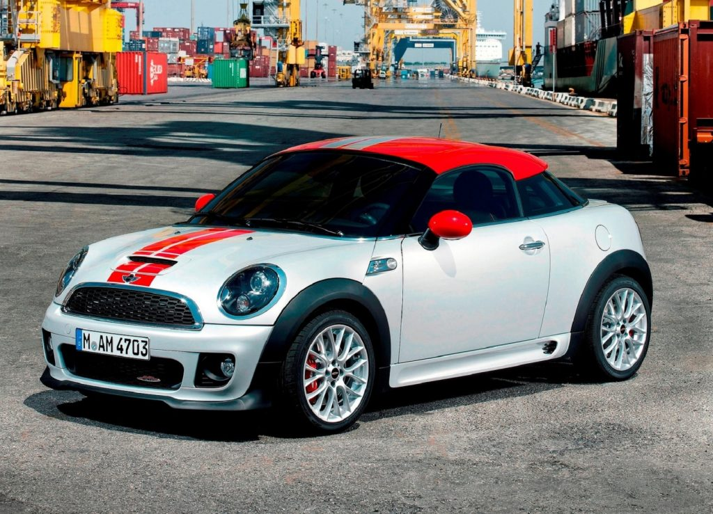 A white-with-red-roof 2013 Mini Cooper Coupe JCW on a shipping dock
