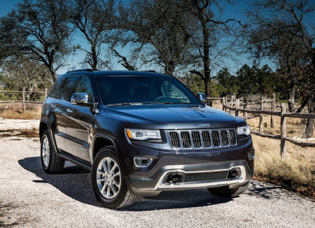 A dark-blue 2014 Jeep Grand Cherokee EcoDiesel Limited 4x4 parked by a plain forest