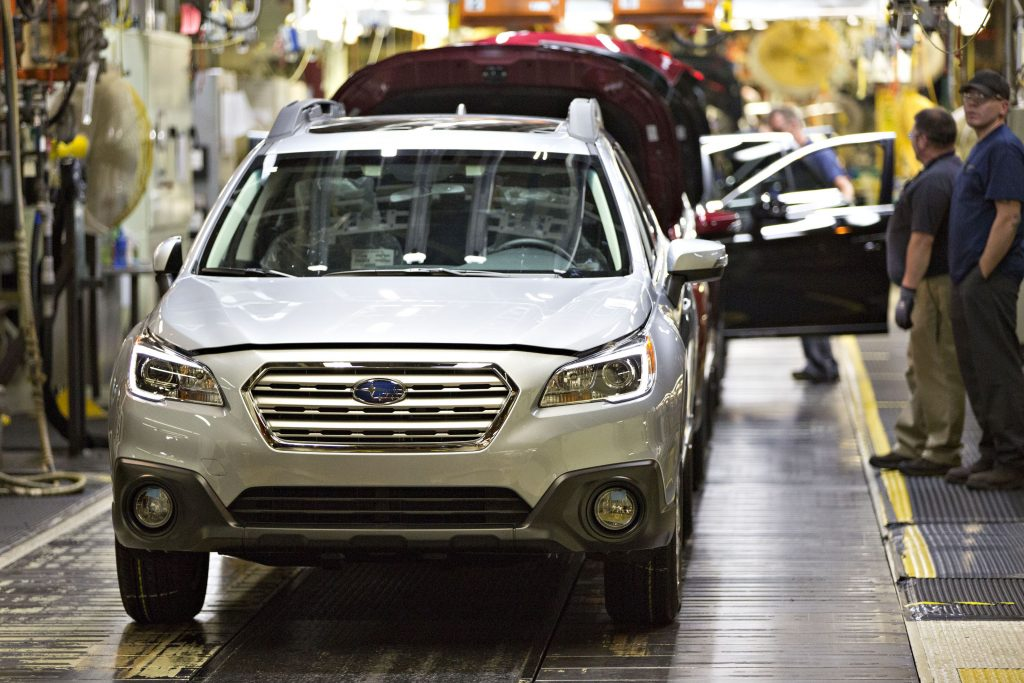 A silver 2016 Subaru Outback SUV on the assembly line
