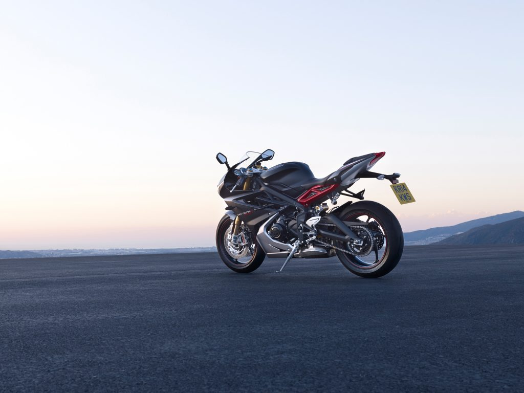 The rear 3/4 view of a black-and-red 2016 Triumph Daytona 675R on a mountainside parking lot