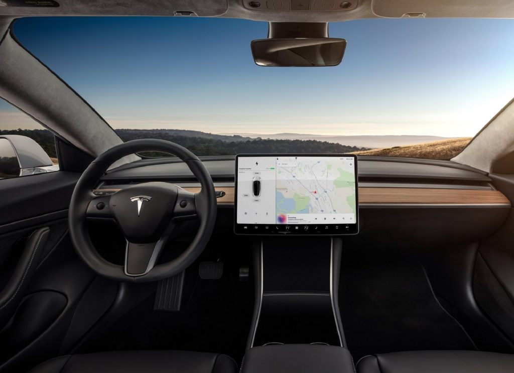 The black front seats and wood-trimmed dashboard of a 2018 Tesla Model 3