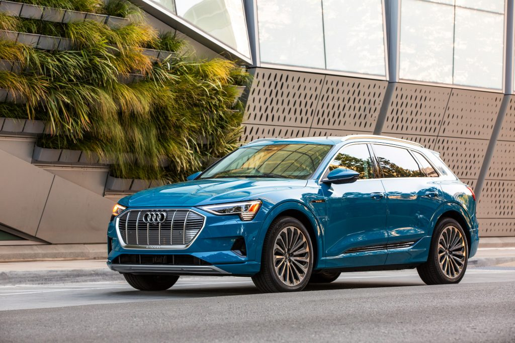 A bright-blue 2019 Audi e-tron electric crossover SUV parked on a street outside a modern building