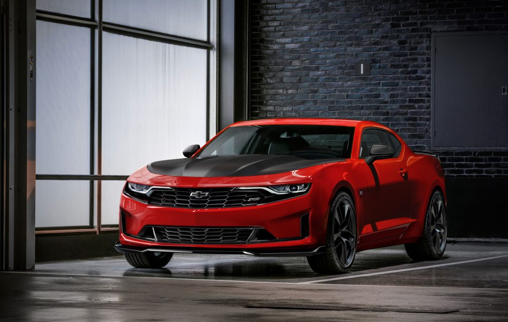 A red 2019 Chevrolet Camaro Turbo 1LE with a black hood in a warehouse