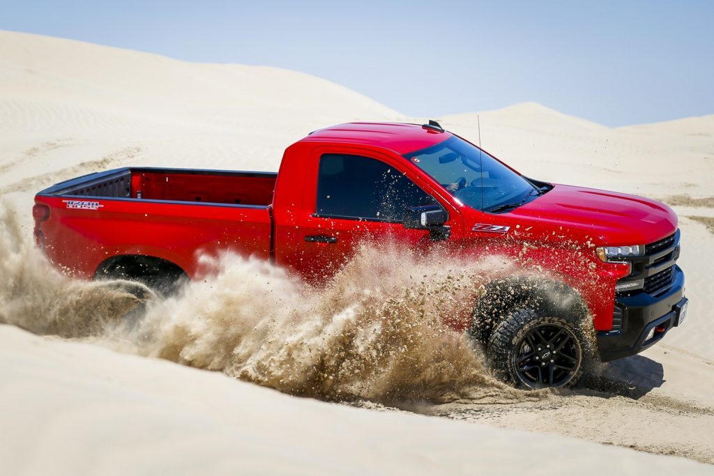 a red Chevy Silverado short bed, single cab pickup kicking up sand on the dunes
