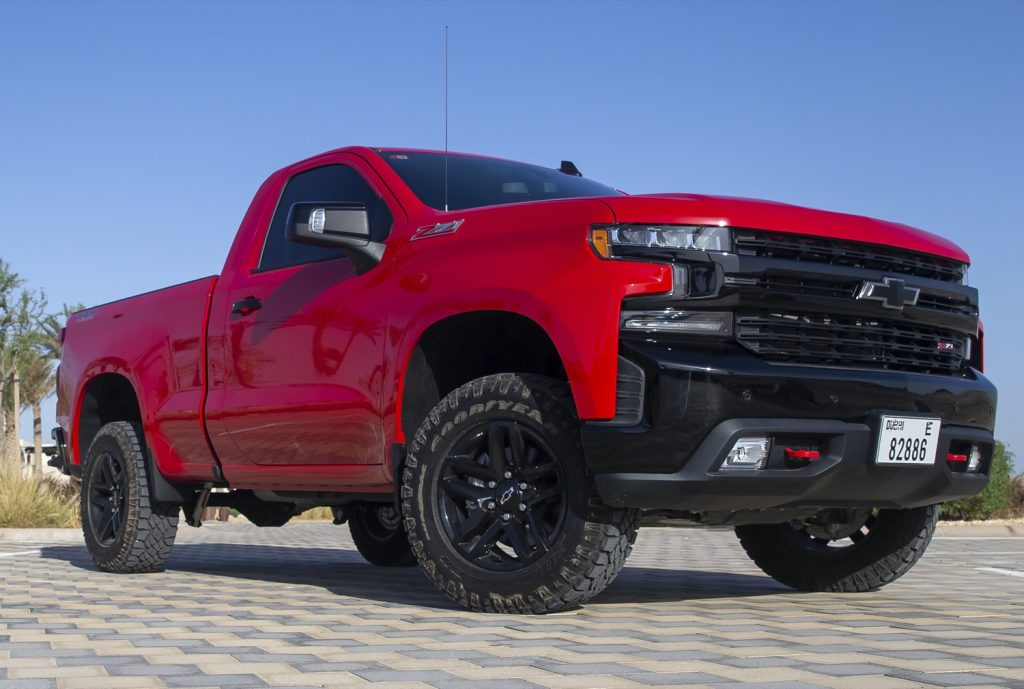 front 3/4 view of red single cab, short bed Silverado.