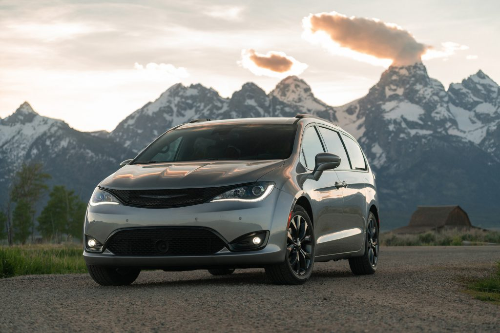 A silver 2020 Chrysler Pacifica Limited minivan parked on gravel in front of snowcapped mountain with the sun behind them
