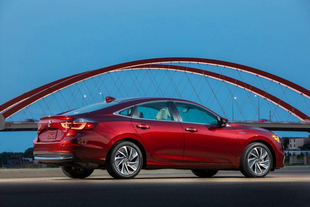 A red 2020 Honda Insight hybrid sedan parked in front of a bridge