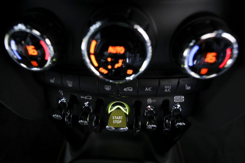 A close-up of the 2020 Mini Cooper SE's dashboard focusing on the push-button start ignition switch