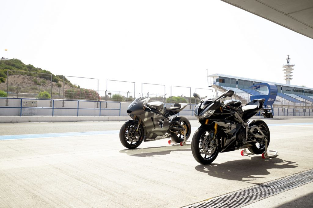 A black-and-silver 2020 Triumph Daytona 765 Moto2 Limited Edition parked next to the gray development mule on a racetrack
