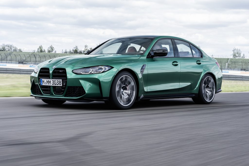 A green 2021 BMW M3 driving on a racetrack