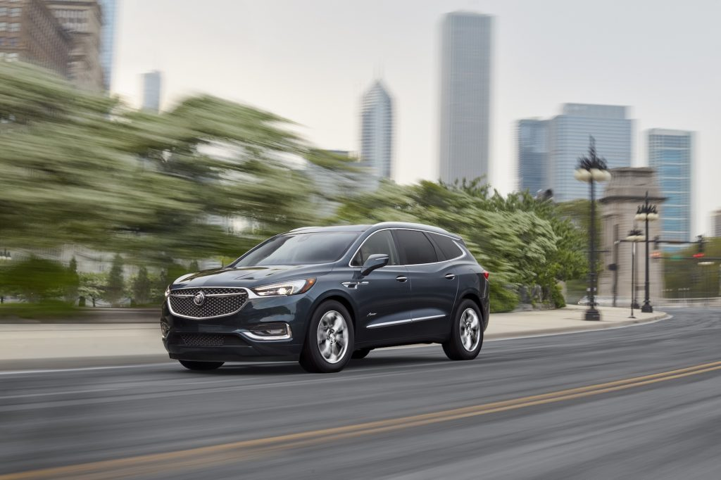 A dark-blue 2021 Buick Enclave luxury midsize crossover SUV traveling on a city street lined with trees and lamp posts