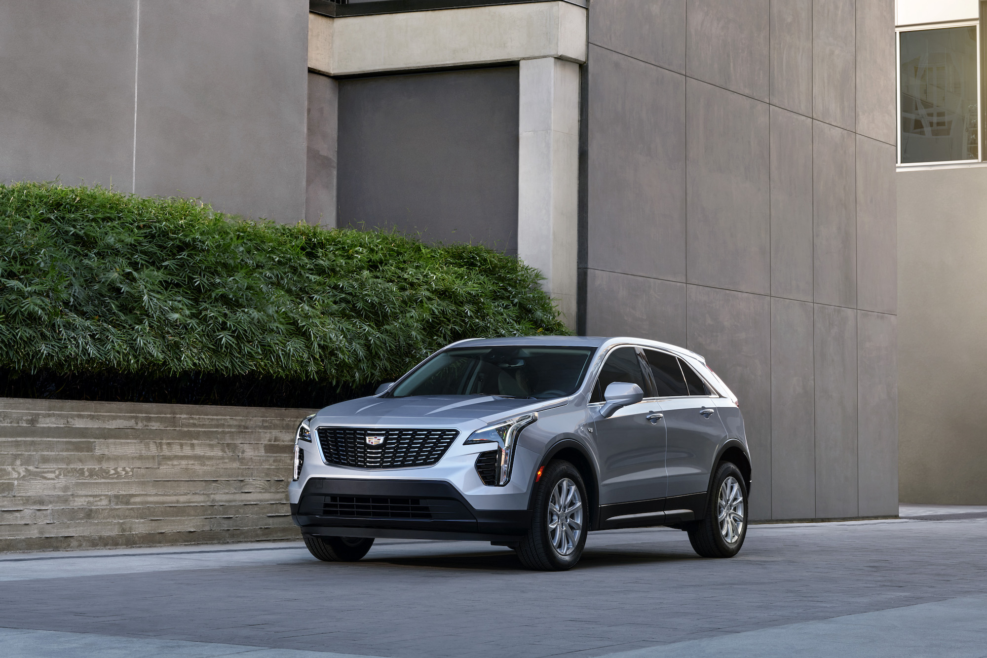 A silver 2021 Cadillac XT4 luxury compact crossover SUV parked next to a brownish-gray concrete modern building with a green hedge