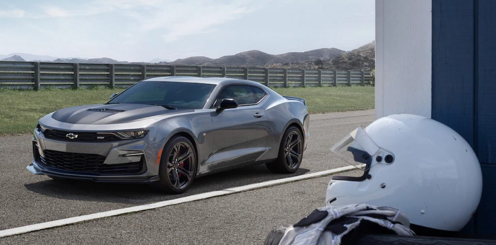 A gray 2021 Chevrolet Camaro SS 1LE on a track with a white helmet in the foreground