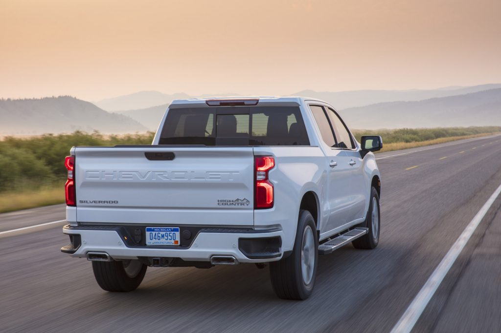 A white 2021 Chevy Silverado High Country four-door pickup truck traveling on a two-lane highway toward mountains on a foggy day