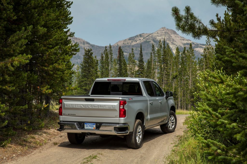 The rear 3/4 view of a silver 2021 Chevrolet Silverado 1500 LT 4x4 in a pine forest