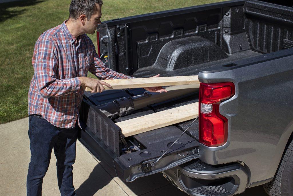 A man loading wood into the 2021 Chevy Silverado's Multi-Flex Tailgate