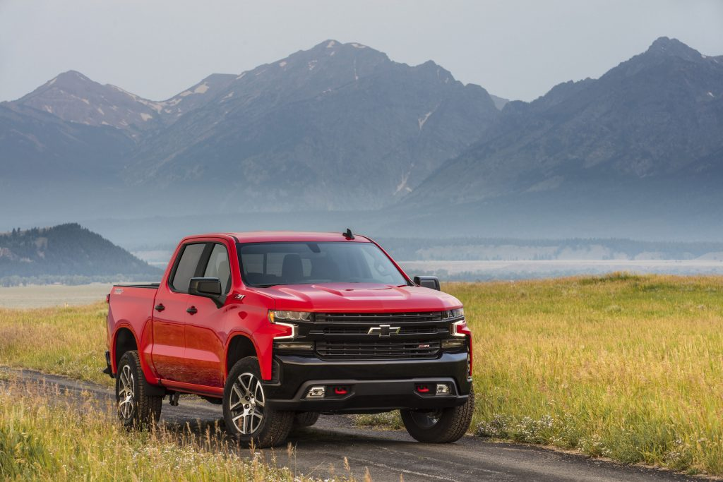 2021 Chevy Silverado Trail Boss in red parked in front of some mountains