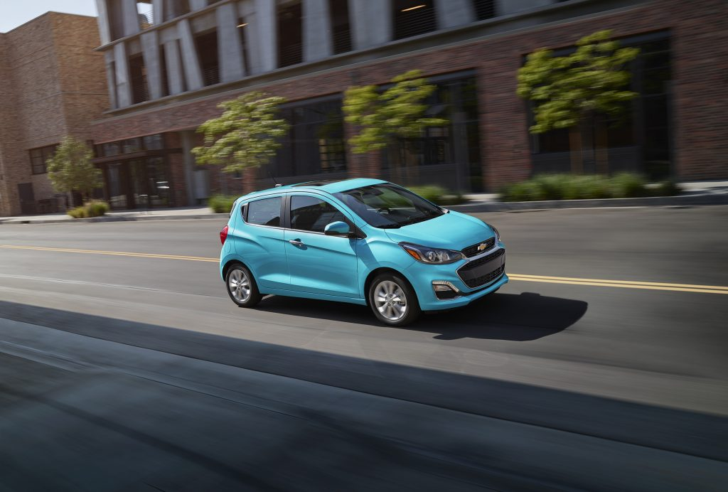 a blue Chevy Spark driving on a city street
