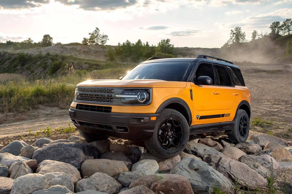 An orange metallic 2021 Ford Bronco Sport compact crossover SUV parked on rocks beside a dirt road