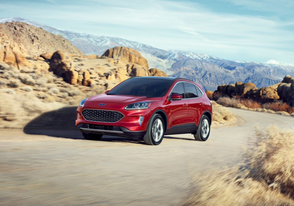 A red 2021 Ford Escape Hybrid drives on a desert mountain road