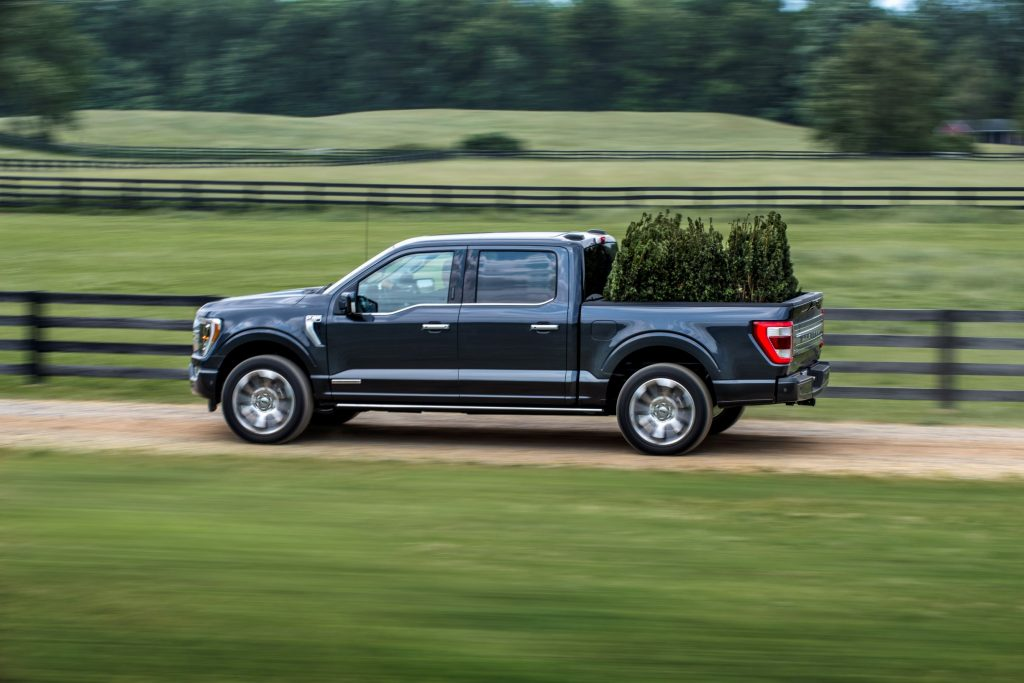 A dark-blue 2021 Ford F-150 PowerBoost Hybrid drives down a field road carrying some trees