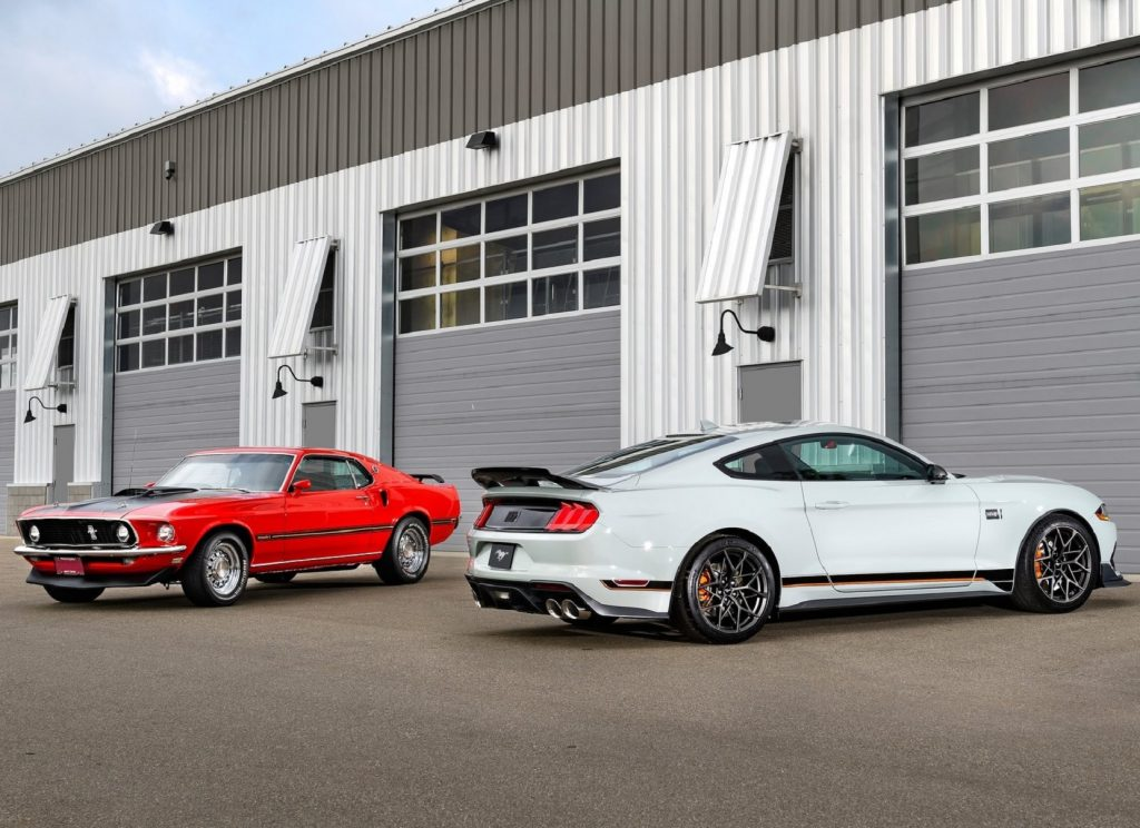 A gray 2021 Ford Mustang Mach 1 with the Handling Package parked with a red 1969 Ford Mustang Mach 1 next to a garage