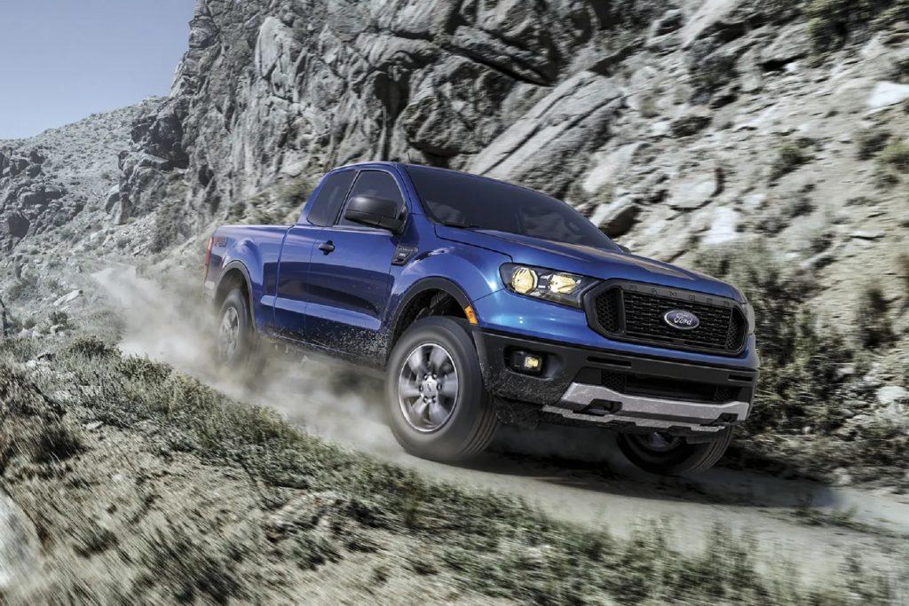 A blue 2021 Ford Ranger XLT SuperCab FX4 drives down a mountainside gravel road