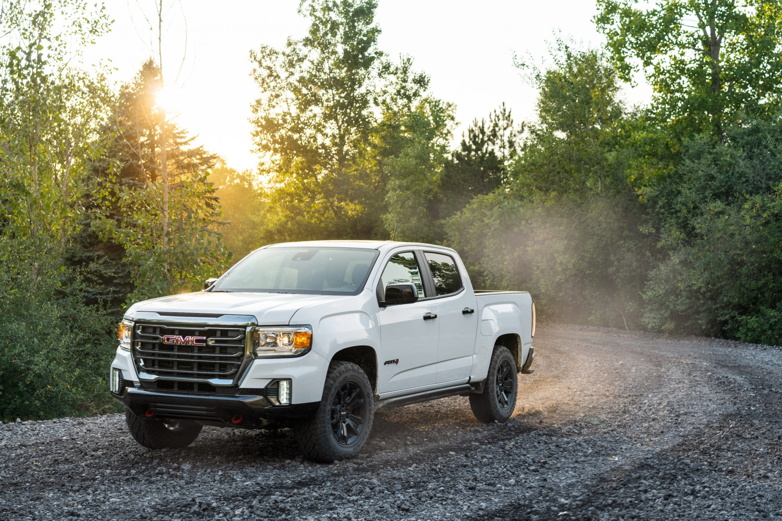 a white 2021 GMC Canyon drives off-road on a gravel trail.