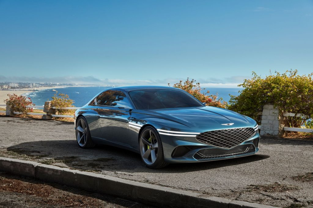 The green 2021 Genesis X Concept parked overlooking a sandy beach