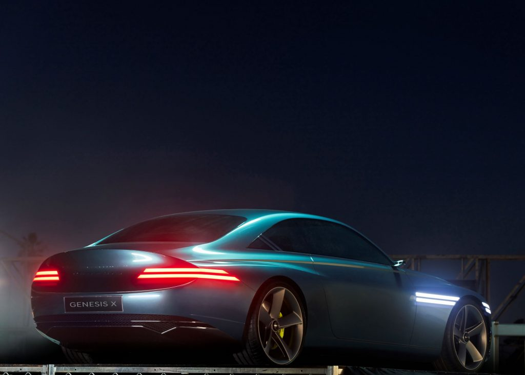 The rear 3/4 view of the green 2021 Genesis X Concept with its lights on at night