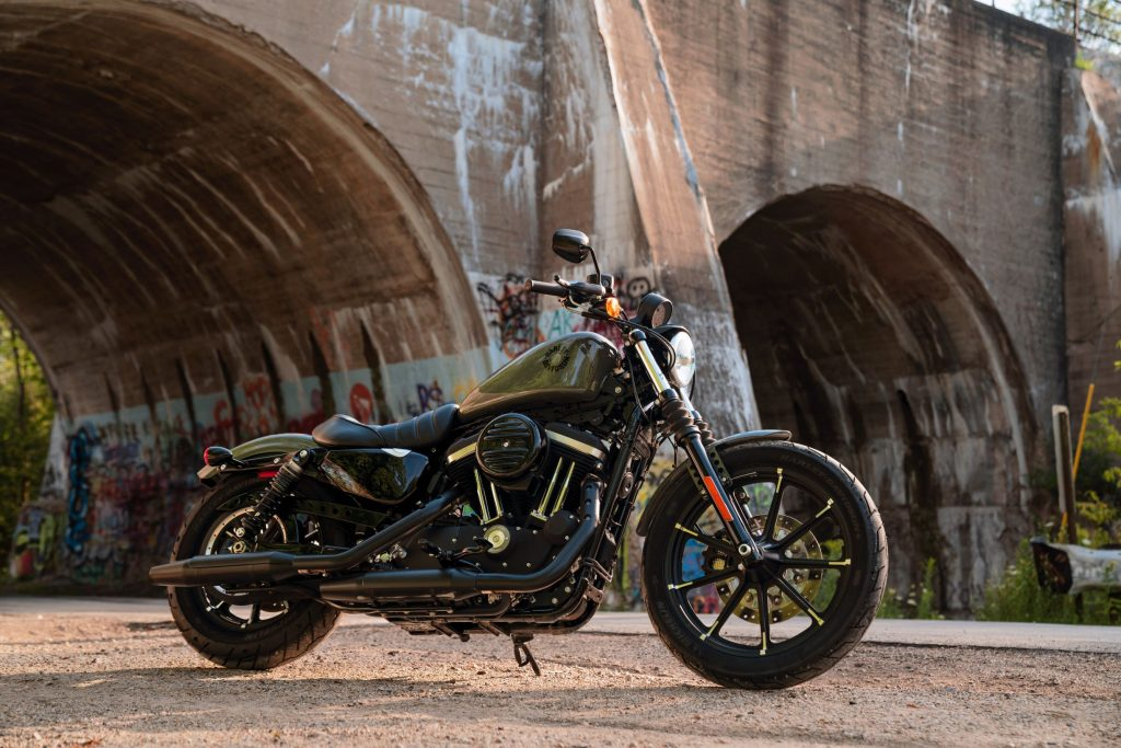 A dark-green 2021 Harley-Davidson Iron 883 by a river-bridge tunnel