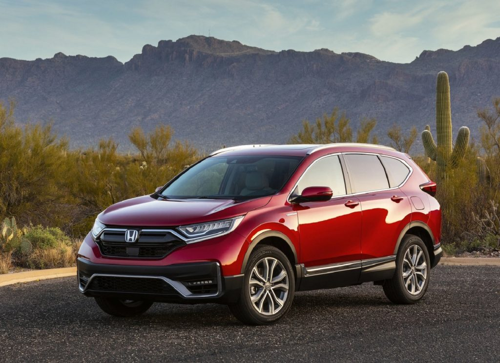 A red 2021 Honda CR-V Hybrid parked on a desert road by the mountains