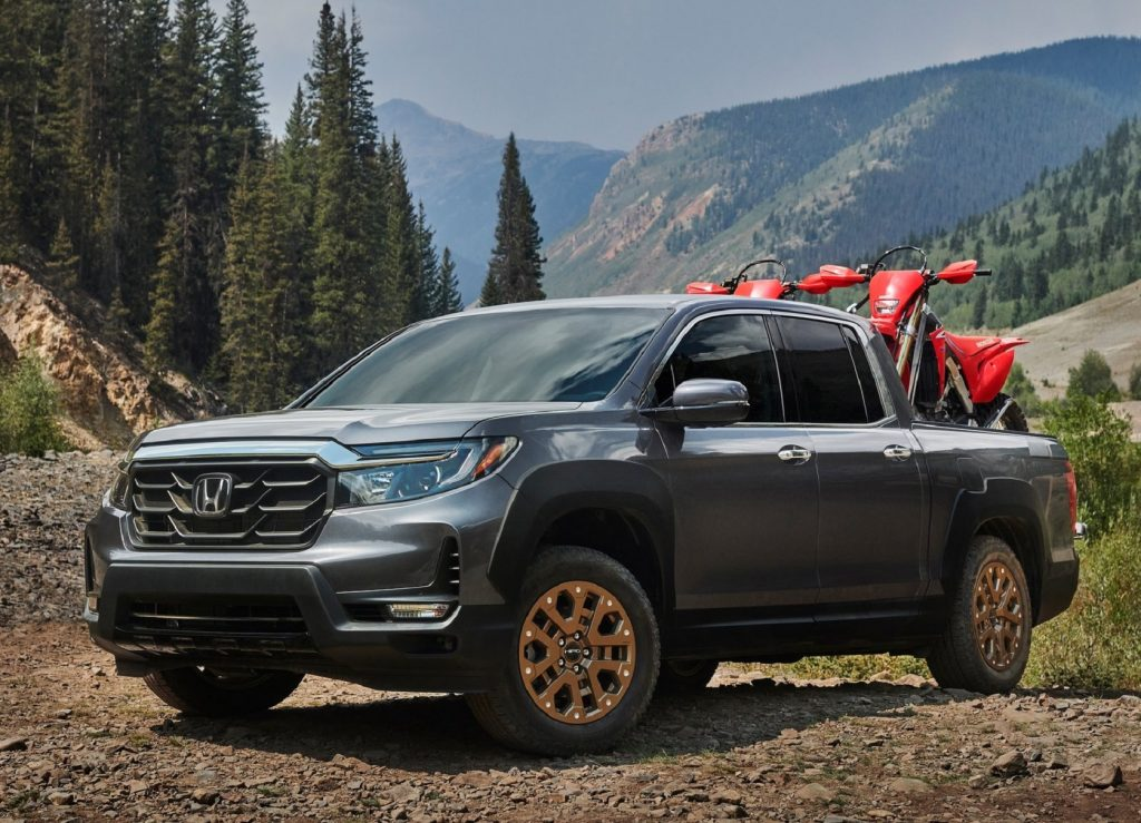 A gray 2021 Honda Ridgeline with bronze HPD wheels and two red dirt bikes in the bed in a mountain forest