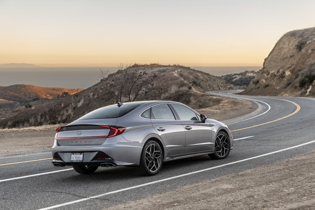 A silver 2021 Hyundai Sonata N Line midsize sedan out for a spin on a curvy two-lane mountain highway overlooking an ocean