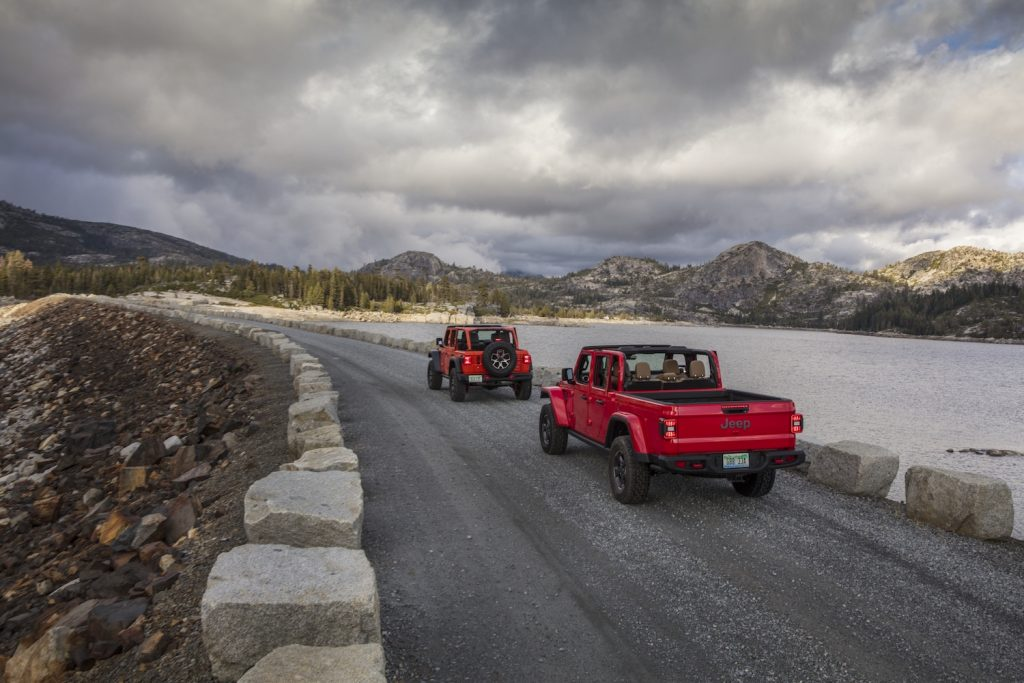 The 2021 Jeep Gladiator and Jeep Wrangler being driven on a cloudy day