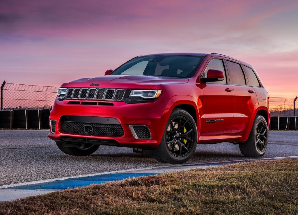 A red 2021 Jeep Grand Cherokee Trackhawk on a racetrack at sunset