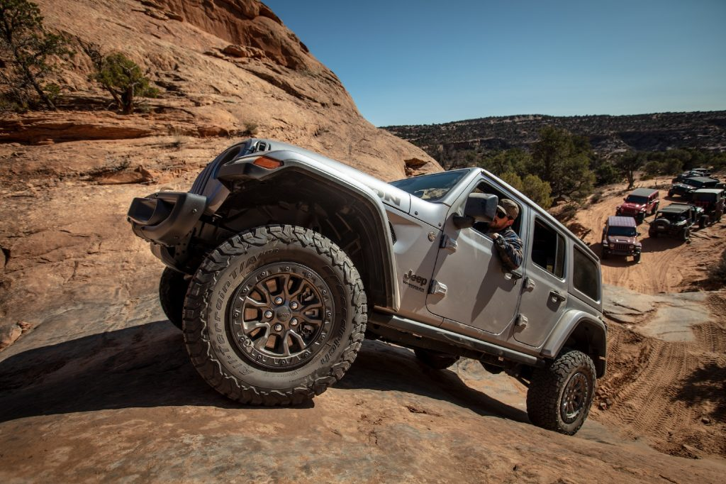 A silver 2021 Jeep Wrangler Rubicon 392 SUV navigates a red-rock mountain on a clear day