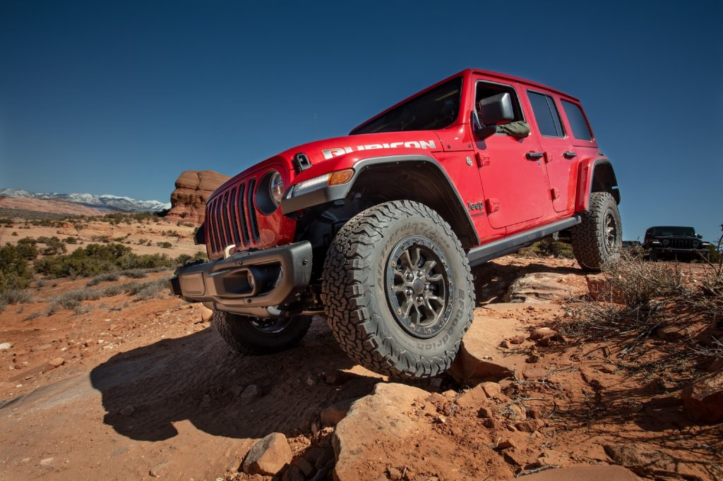 A red 2021 Jeep Wrangler Rubicon 392 SUV parked on rocks on the side of a hill