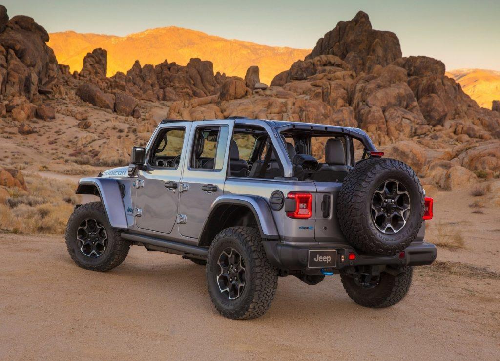 The rear 3/4 view of a gray 2021 Jeep Wrangler Rubicon 4xe in the desert mountains