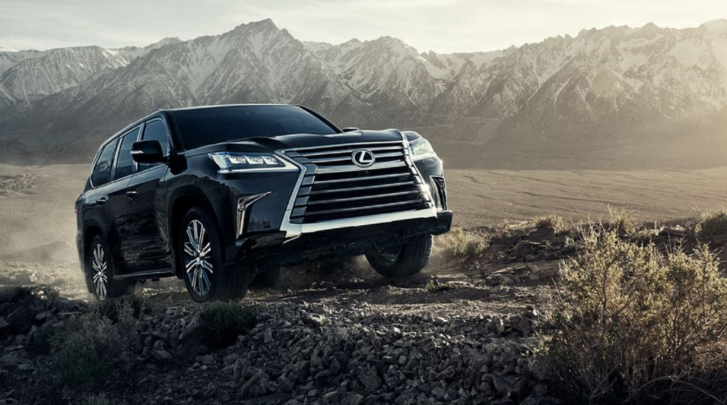 A black 2021 Lexus LX 570 climbs up a hill in the desert by some mountains