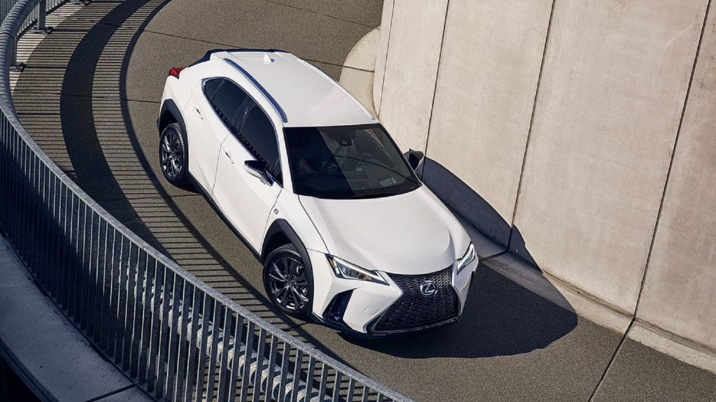An overhead of a white 2021 Lexus UX 250h driving down a curving road