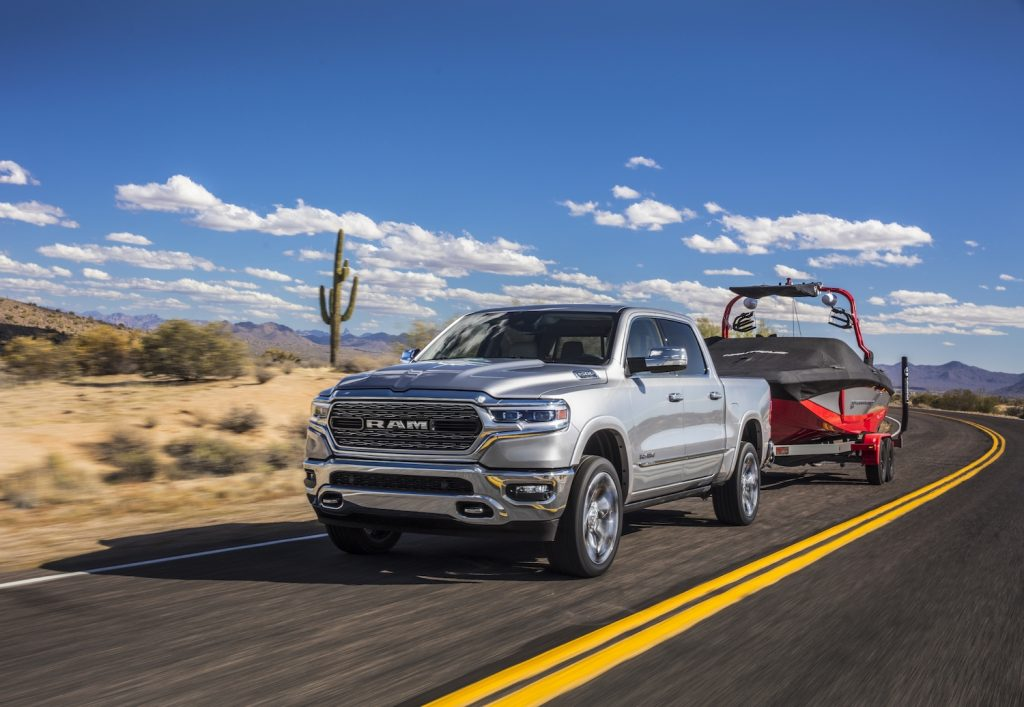 Pictured is one of the best trucks for towing, the 2021 Ram 1500 Limited, as it tows a boat.