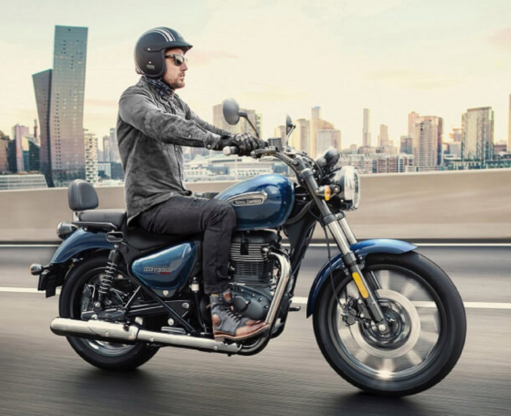 A rider takes a dark-blue 2021 Royal Enfield Meteor 350 Supernova down a wet city highway