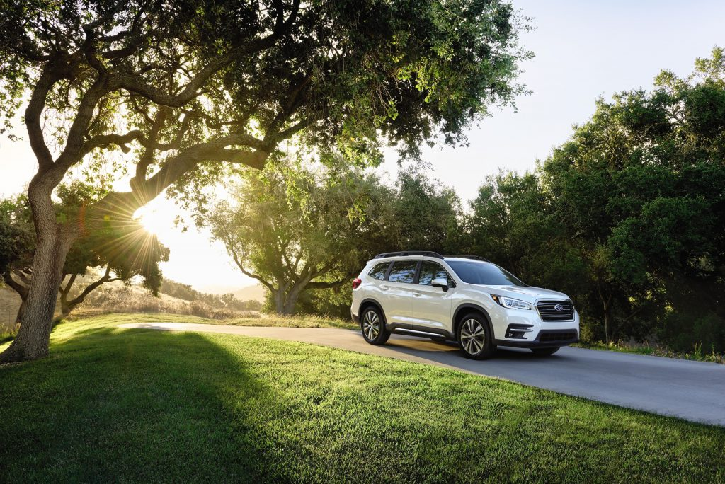 A white 2021 Subaru Ascent SUV driving down a tree-lined road