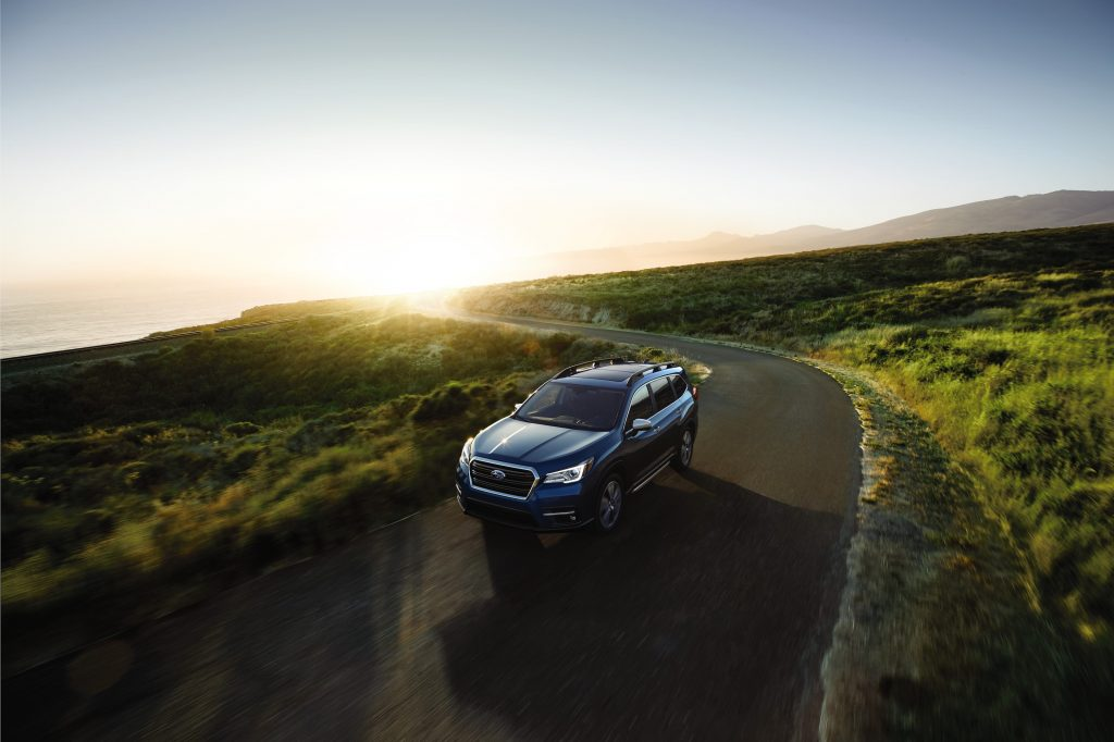 A blue 2021 Subaru Ascent SUV driving down a country road